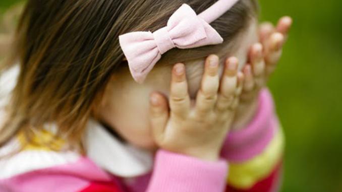Shy child closing eyes